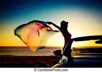 Silhouette of young woman at the beach. Girl with flying...