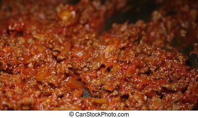 Minced meat being mixed in a pan by spoon