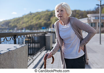 Retired woman having lower back pain during the promenade -...