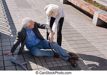 Tired aging man falling down on the road - Extend a helping...