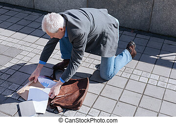 Bewildered man quickly vetting his handbag in the park -...