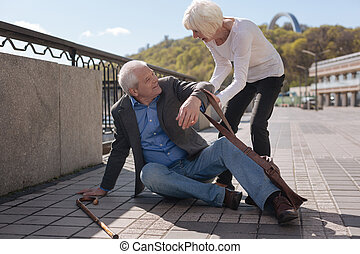 Merry pensioner sitting on the street and receiving help -...