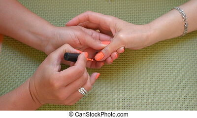 Manicure orange nail polish. - Manicure applying orange nail...