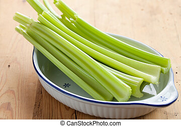green celery sticks on kitchen table - photo shot of green...