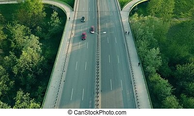 Cars and cyclists moving along highway in the evening -...