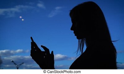 Silhouette of female using phone. Black silhouette of female...