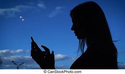 Silhouette of female using phone. Black silhouette of female...
