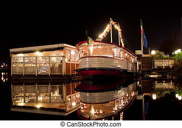 Ship and cafes are at night on the black waters of Lake...