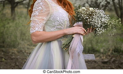 Red-haired beautiful woman in a luxurious dress is holding a spring bouquet in the flowering garden