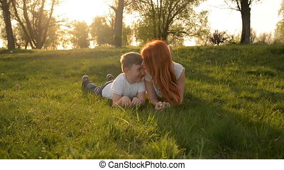 Mother and son having fun outdoors lying on grass