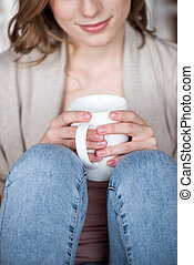 Woman holding cup - Close-up partial view of young smiling...