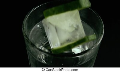 Slow motion. In a glass of water drops ice and cucumber
