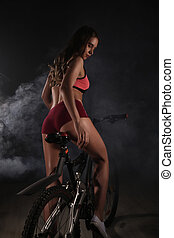 Young sporty woman with bicycle on a gray background with...