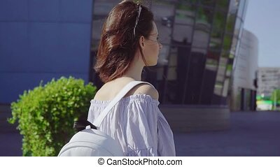 Young Beautiful Female with Curly Hair and Backpack at the Modern Shopping Mall.