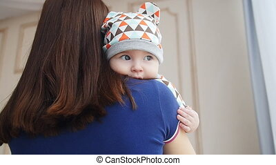 Young woman holding baby boy in her arms - Young woman...