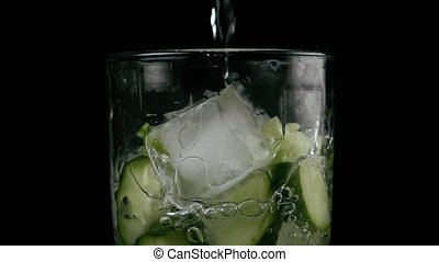 Slow motion. A glass filled with soda on a black background...