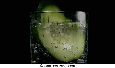 Slow motion. A cucumber slice falls into a glass - Slow...