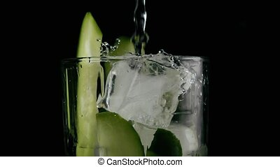 Water is poured into a glass with cucumber and ice. Slow motion