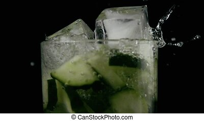 The ice falls into the water with the sliced cucumber. Slow mo