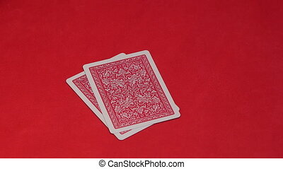 Human hand opening two cards in poker game.