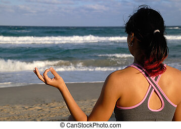 Young Woman Practicing Yoga on the Beach - Woman practicing...