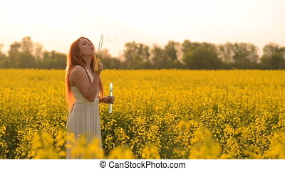 Young red-hair woman blowing bubbles at the camera outdoors in summer meadow