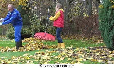 man woman rake autumnal leaves garden. Season work outdoor....