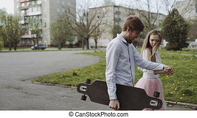 Young couple in love walking in summer park holding hands. Woman in pink tutu skirt man with longboard in hands Three-axis Gimbal stabilized tracking shot