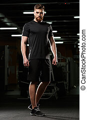Serious handsome sports man standing and posing in gym -...