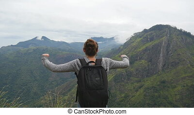Woman tourist standing on edge of beautiful canyon, victoriously outstretching arms up and enjoying freedom. Young female hiker with backpack reaching up top of mountain and raised hands. Slow motion