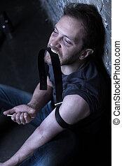 Mad drug user holding syringe in the dark lighted room