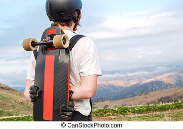 A young man in a helmet wearing gloves with a board in his...