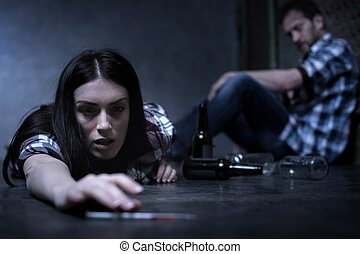 Overdosed addict lying on the floor in the dark place