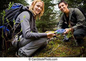Finding a Geocache - Two people finding a geocache in the...