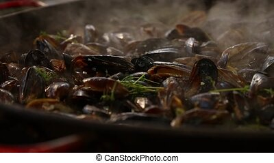 Cooking mussels at big frying pan with steam - Cooking...