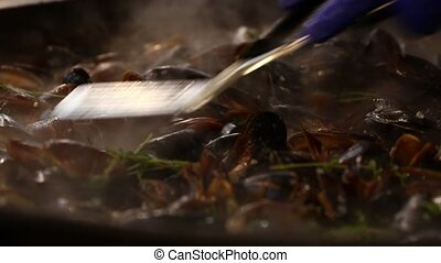 Cooking and stirring mussels at big frying pan - Cooking...