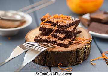 Healthy craft chocolate bars with orange rind and cocoa on wood slabs