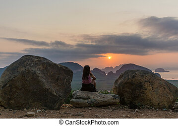 Woman watching sunrise on Phang Nga bay - Woman sitting and...