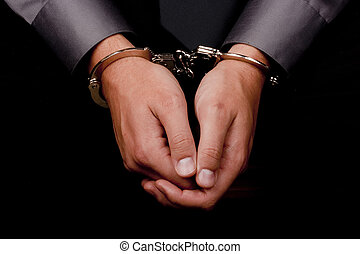 Arrested for questioning - Close-up of hands handcuffed,...