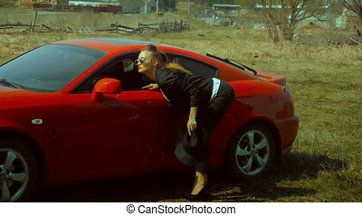 lady near the Red sports car looks in the mirror - charming...
