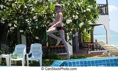 kid playing ball in the pool. sports outdoors. Jump into the...