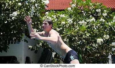 guy playing ball in the pool. sports outdoors. Jump into the...
