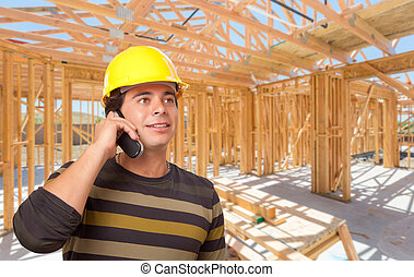 Hispanic Contractor Using Phone On Site Inside New Home Construction Framing.