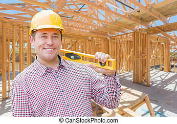 Contractor With Level On Site Inside New Home Construction Framing.