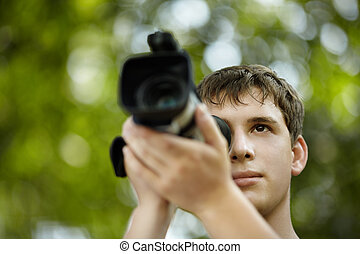 young videographer - teen with camcorder capturing,...