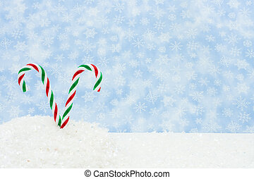 Winter Scene - Two green and red candy canes in a snow bank,...