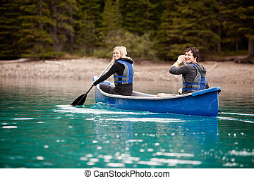Canoe Adventure in Lake - A man and woman paddling in a...