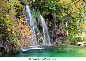 Autumn Waterfall in Forest - Scenic waterfall and small lake...