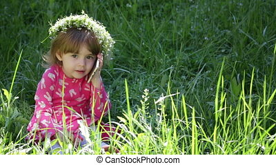 Beautiful little girl with flowers head wreath and talking on her cell phone in the park