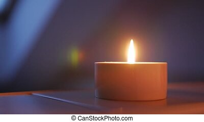 Close-up of a candle, shallow depth of field with focus on the wick and flame.